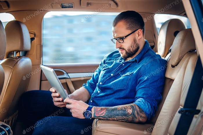 A man in eyeglasses with tattoo on his arm using portable tablet PC on a back seat of a car.
