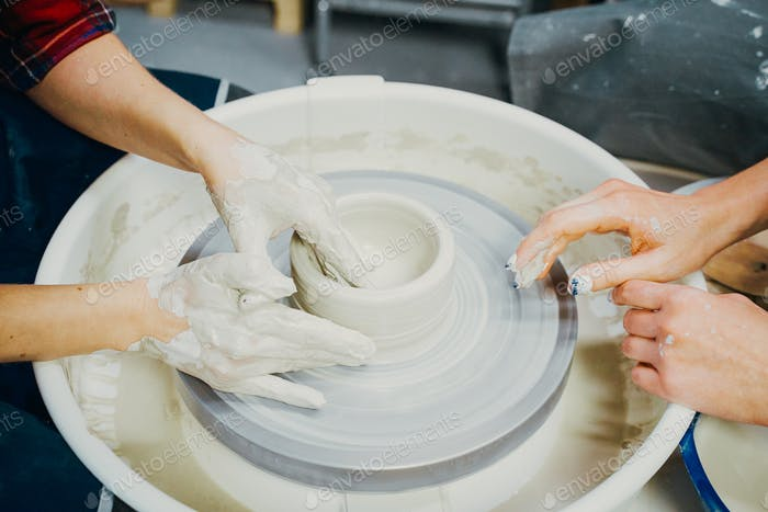 Woman making ceramic pottery, four hands close-up, focus on potters, palms with pottery