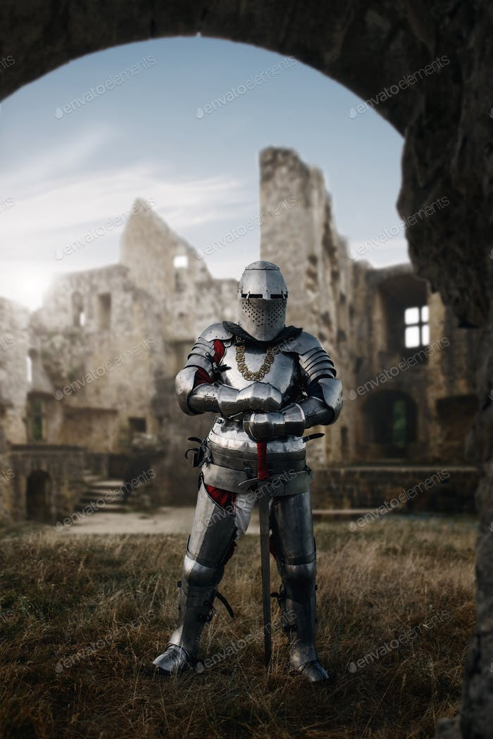 Knight in armor and helmet poses in castle