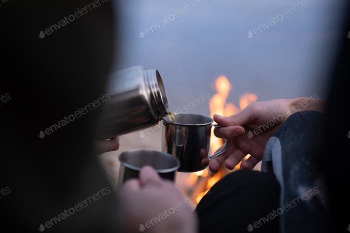 Crop couple pouring hot tea in countryside