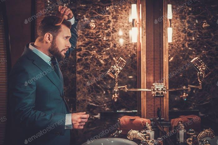 Уверенный хорошо одетый человек расчесывает волосы в роскошной ванной интер