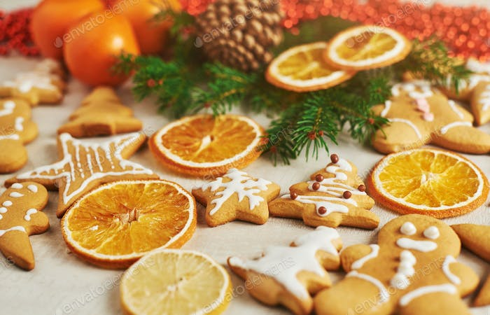 Christmas gingerbread cookies and dried orange and spices on white table. Chairs Christmas trees