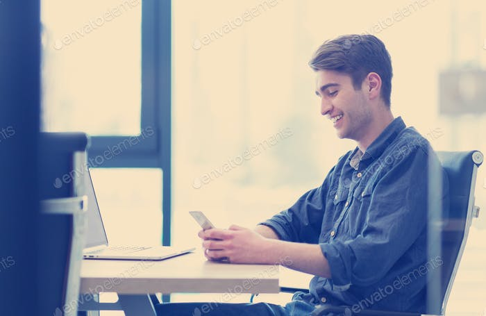 Young casual businessman using smartphone