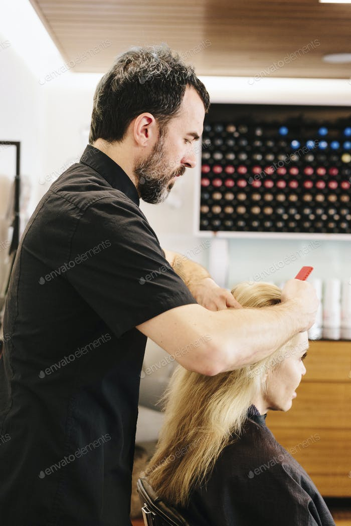 A hair stylist combing out a client's hair.