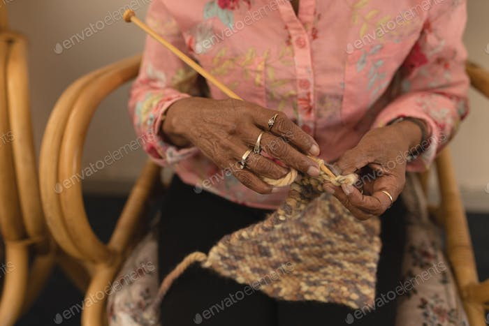 Mid section of senior woman knitting with yarn at home