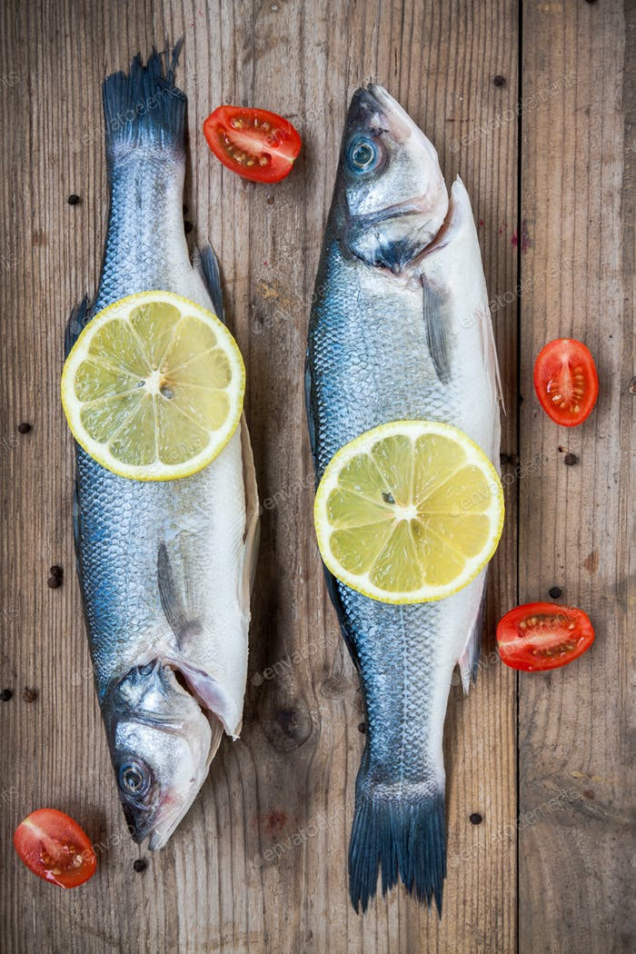 Two raw seabass fish with lemon and cherry tomatoes on wooden ba