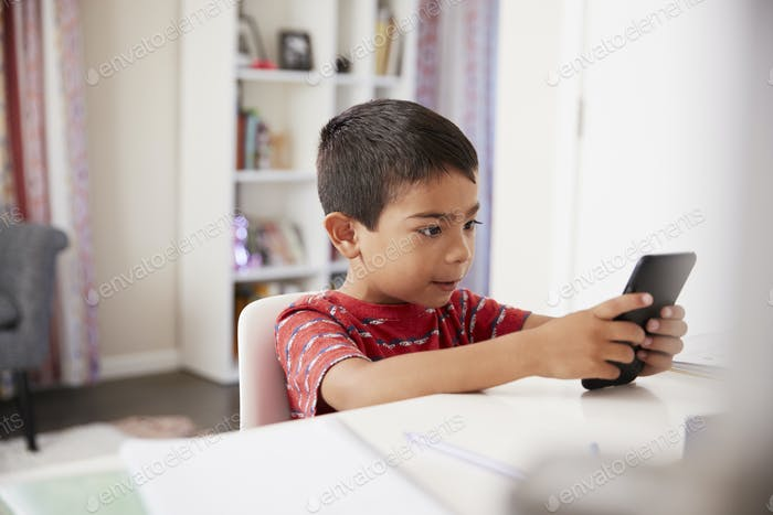 Young Boy Sitting At Desk In Bedroom f Mobile Phone Whilst Doing Homework