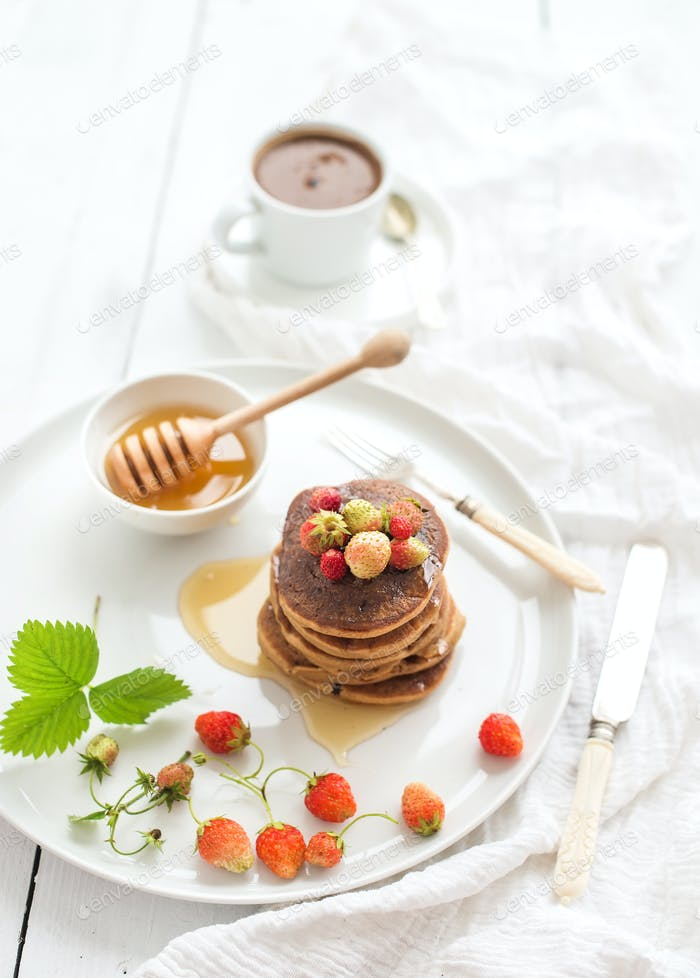 Breakfast set. Buckwheat pancakes with fresh garden strawberries, honey and cup of coffee