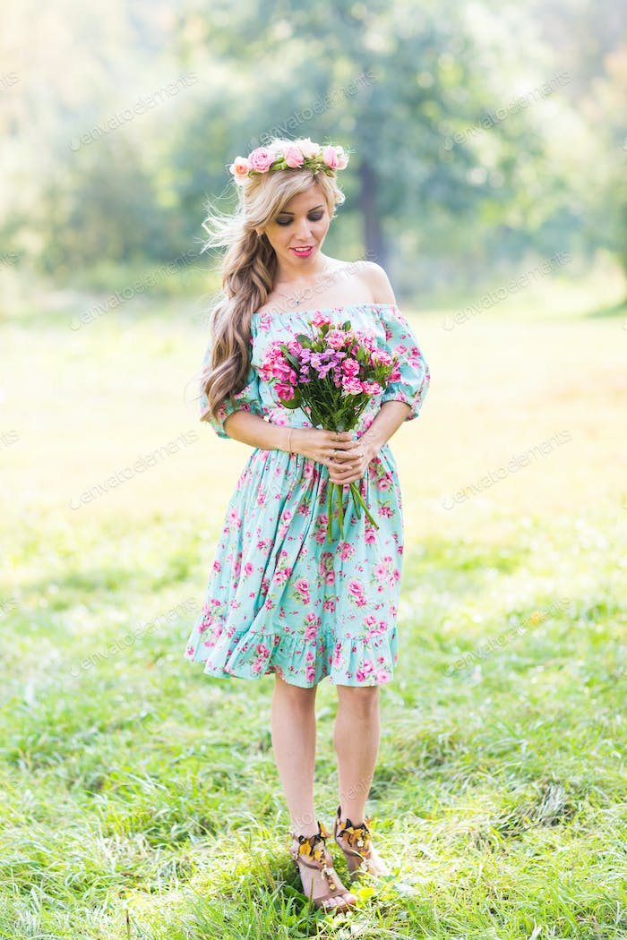 Beautiful blonde girl holding bouquet of flowers at the countryside