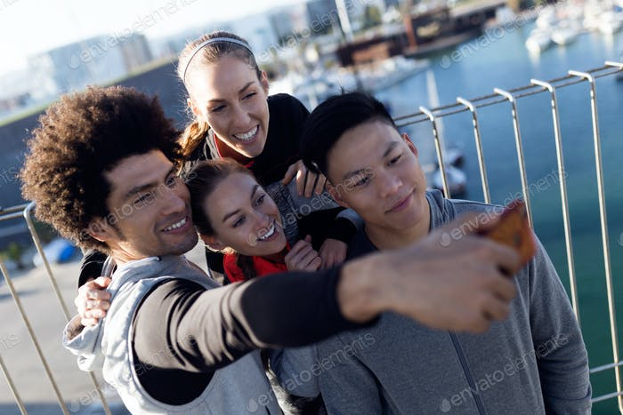 Fit and sporty team using mobile phone in the city.
