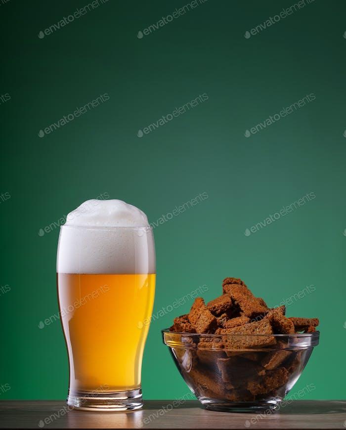 Glas helles Bier und Teller von Crackern mit Gewürzen auf grünem Hintergrund