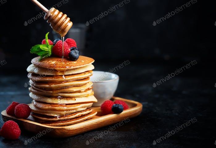 Pfannkuchen mit Heidelbeeren, Himbeeren, Minze und Honig zum Frühstück