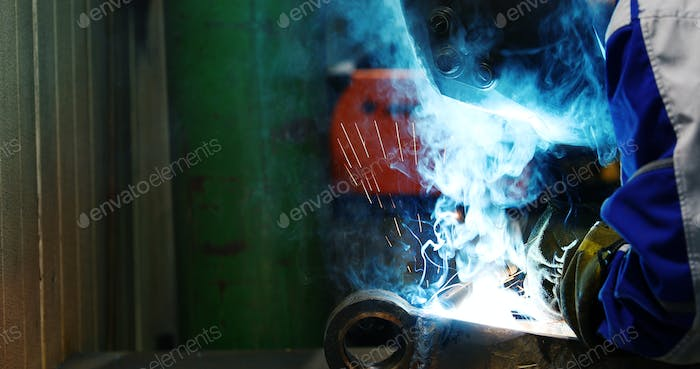 Industrial Worker at the factory welding metal closeup