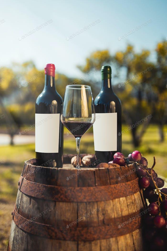 Bottles and goblet of wine on a barrel