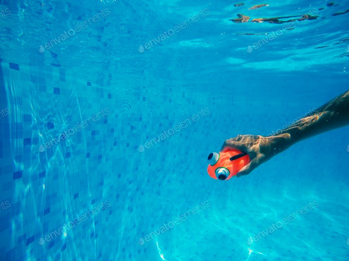 Child playing with generic rubber fish toy in swimming pool