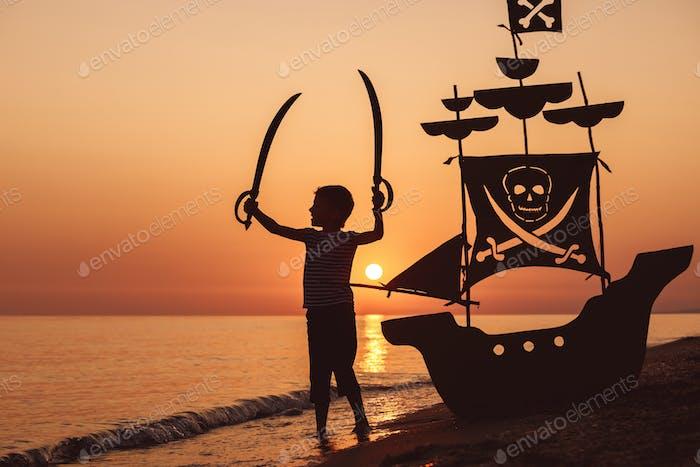 Ein glücklicher kleiner Junge spielt am Strand bei Sonnenuntergang Zeit.