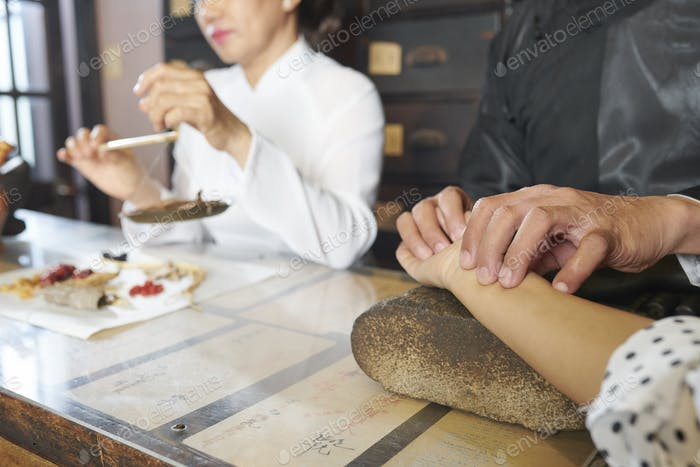 Chinese medicine practitioner taking pulse of customer