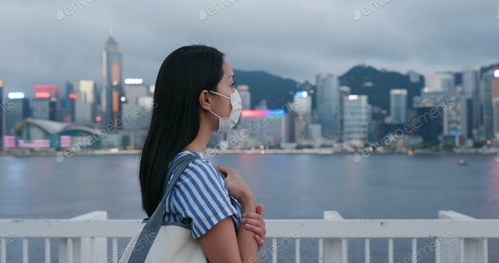 Woman wear face mask and look at the city
