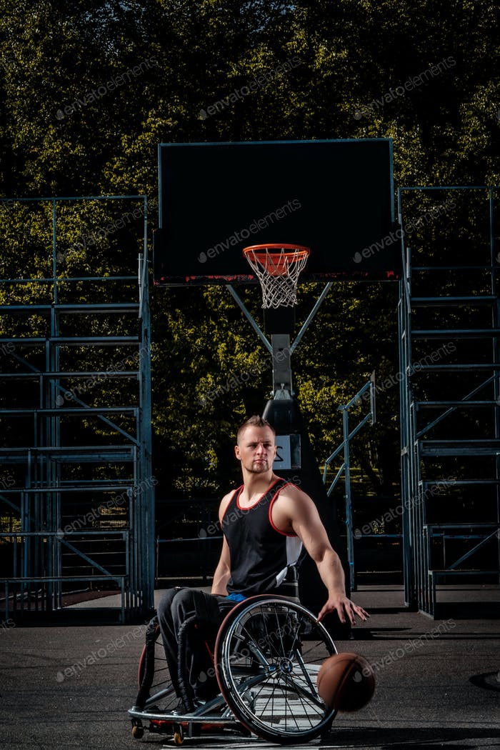 Cripple basketball player in a wheelchair plays on open gaming ground.
