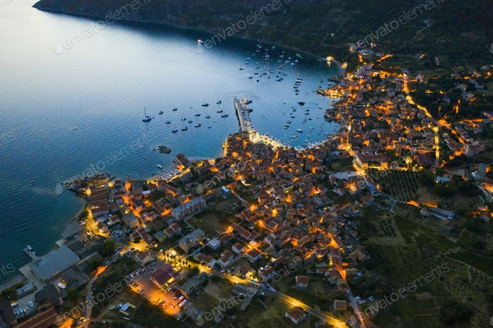 Aerial view of seaside town of Komiza in Croatia at night with street lights on