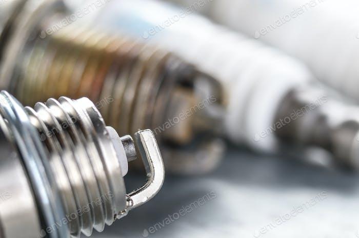 Neue und gebrauchte Zündkerzen für Verbrennungsmotor auf Metall