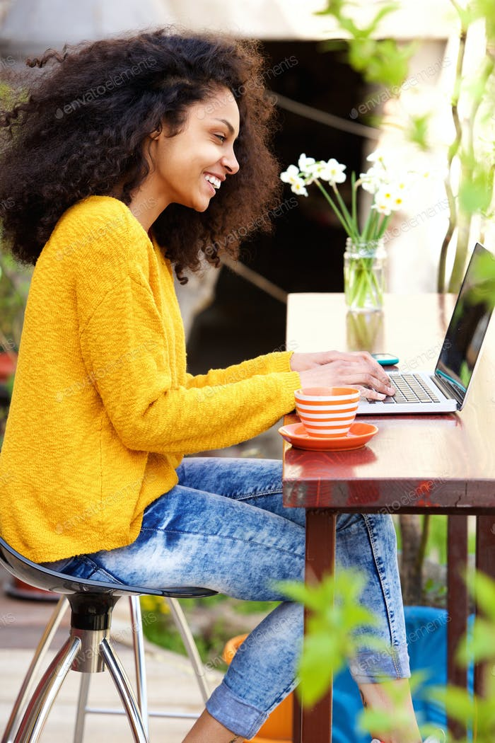 Young woman sitting at outdoor cafe using laptop