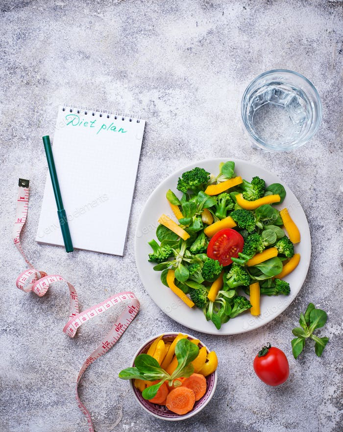 Healthy vegetable salad, water and measuring tape