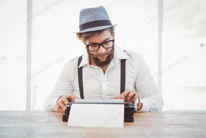 Hipster wearing eye glasses and hat working on typewriter at desk in office