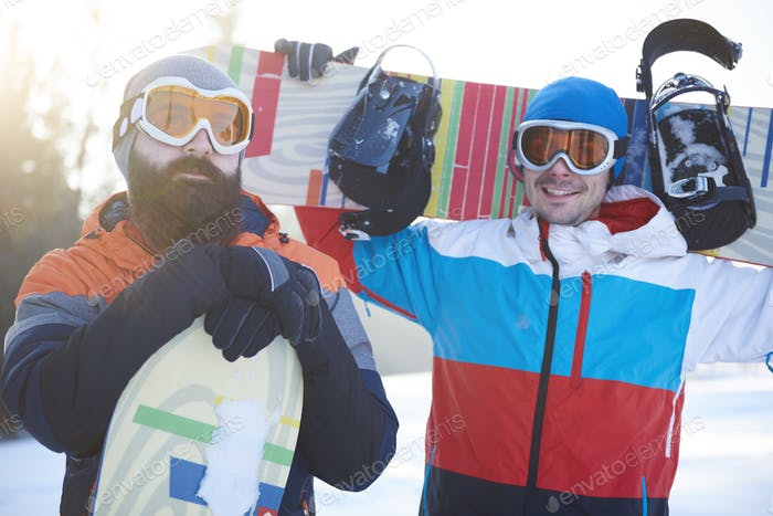 Waist up of two male snowboarders