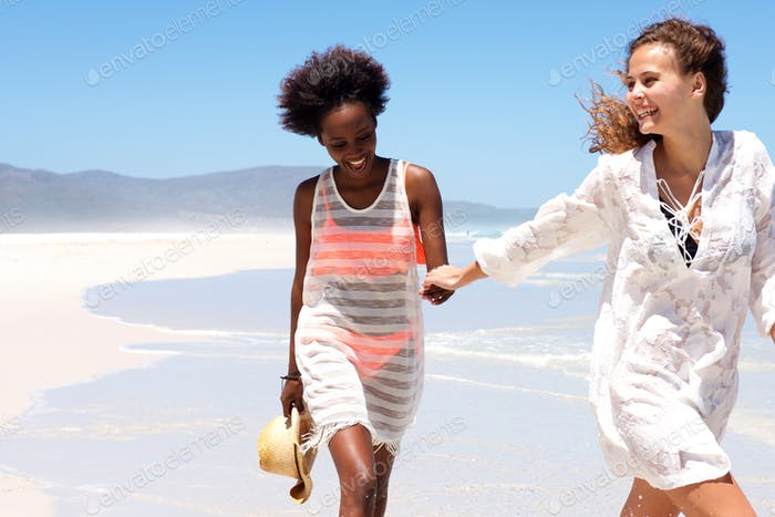 Smiling young women walking together at the seashore