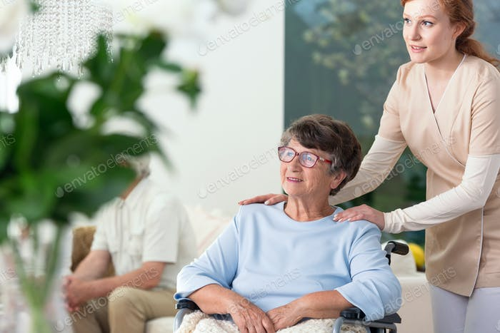 Caregiver taking care of disabled elderly woman in a wheelchair