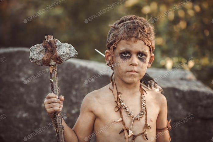 Höhlenmensch Junge mit primitiven Waffe Jagd im Freien