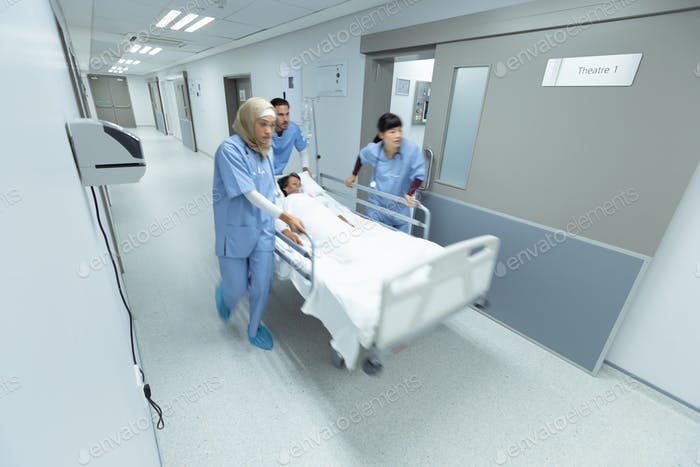 Side view of diverse medical team pushing emergency stretcher bed in corridor at hospital
