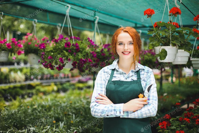 Beautiful smiling florist in apron standing with garden scissors in hand