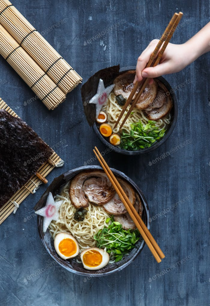 Hand with chopsticks try miso ramen