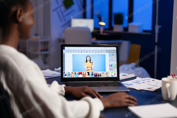 Dark skin freelancer retoucher woman working overtime on editing software