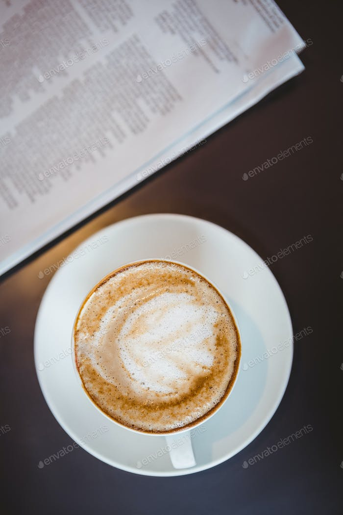 Nahaufnahme Blick auf einen Cappuccino neben einer Zeitung