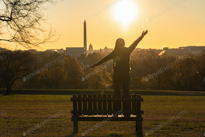 Back side of asian woman standing and Lifting hands for success over the Washington DC Landmark