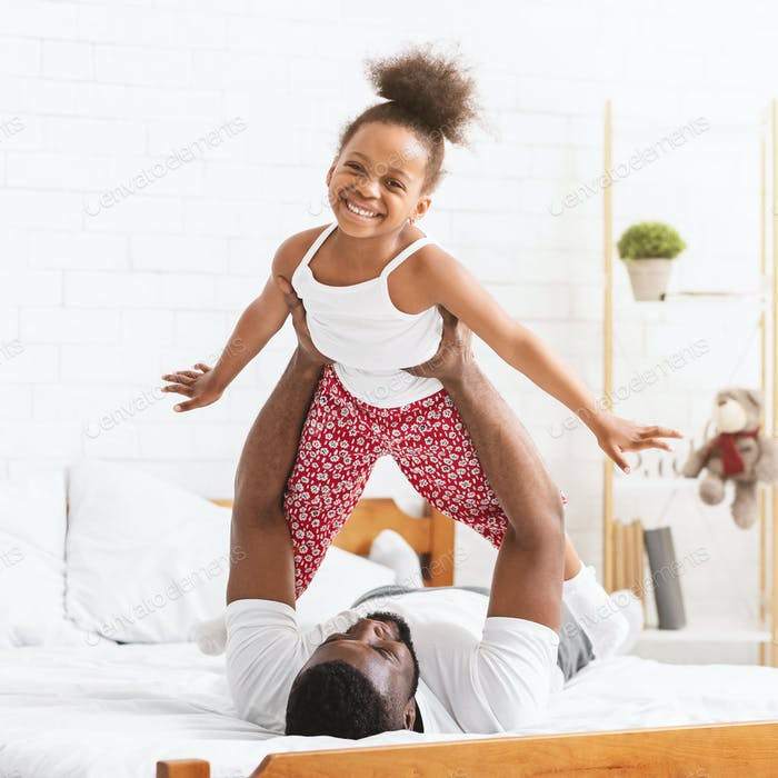 Black dad lifting kid up, playing together in bed