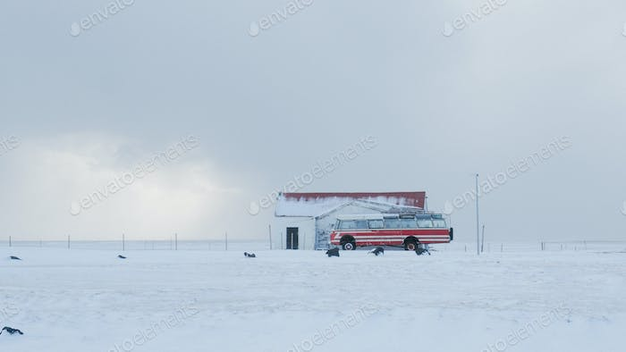 Picture of a red bus with a snowstorm just breaking
