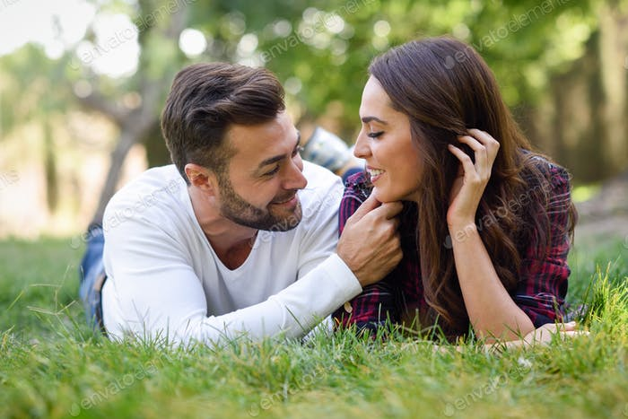 Thumbnail for Beautiful young couple laying on grass in an urban park.