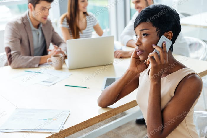 Businesswoman sitting and talking on mobile phone in office