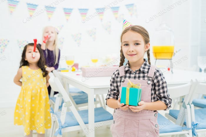 Smiling girl in party hat holding blue gift box