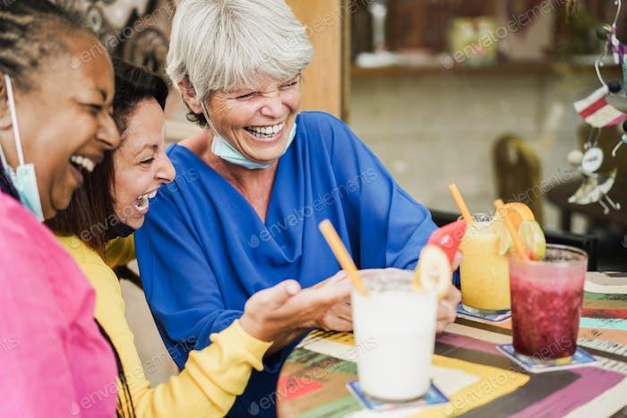 Happy multiracial senior woman using mobile phone at bar during coronavirus outbreak