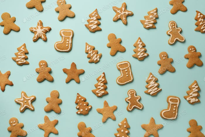 Homemade christmas cookies on blue background. Pattern of gingerbread men, snowflake, star, fir-tree