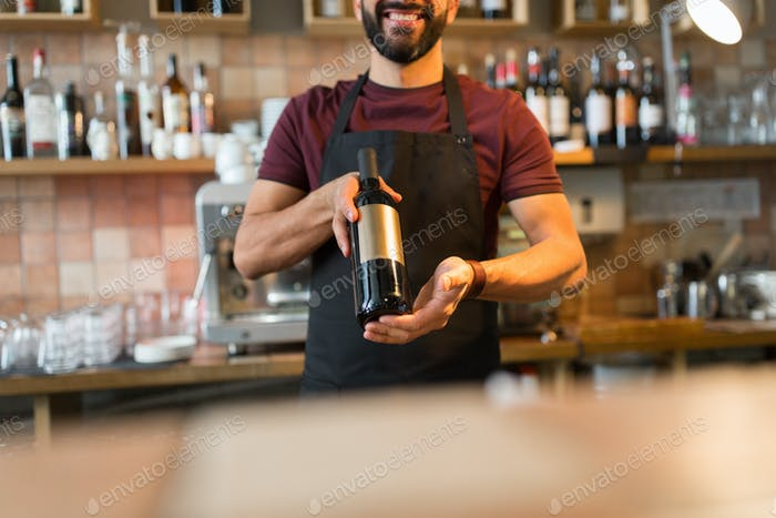 happy man or bartender with bottle of wine at bar