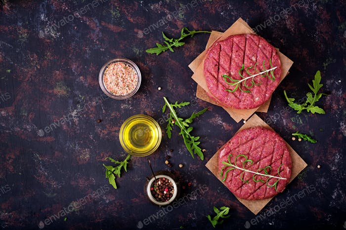 Fresh raw homemade minced beef steak burger with spices on black background