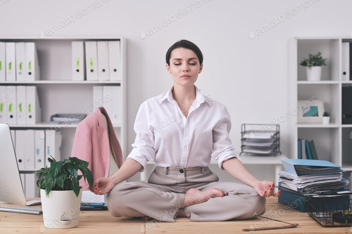 Pretty young barefoot businesswoman in formalwear sitting in pose of lotus