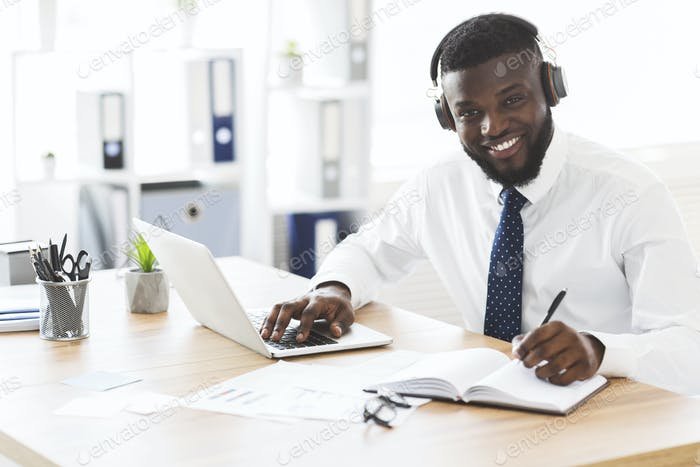 Happy black businessman learning foreign language online