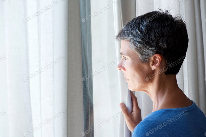 middle age woman peeking out of window